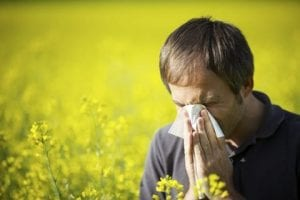 man blowing nose hayfever